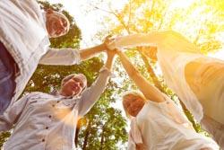 Erfolgreiches Business Team macht zusammen High Five in der Natur im Sommer
